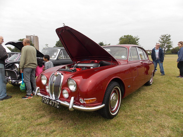BRITISH RED JAGUAR 1964 MOTOR CAR OR AUTOMOBILE  WITH PEOPLE STANDING NEXT TO IT AT  A CAR AND STEAM SHOW IN AN EAST LONDON BOROUGH SUBURB STREET PARK VENUE FESTIVAL EVENT ENGLAND