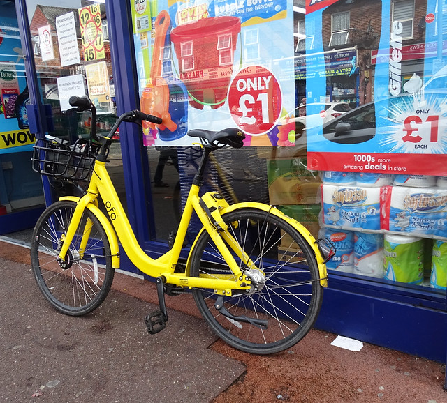 YELLOW BICYCLE ON THE SIDEWALK OR PAVEMENT OUTSIDE A BLUE FRONTED SHOP OR STORE ON AN EAST LONDON BOROUGH SUBURB STREET ENGLAND DSC03039