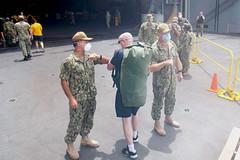 Adm. John C. Aquilino, left, and Fleet Fleet Master Chief James Honea welcome Hospital Corpsman 1st Class Joshua Graddy, returning from off-ship quarantine, aboard USS Theodore Roosevelt (CVN 71). (U.S. Navy/MC3 Dartanon D. Delagarza)
