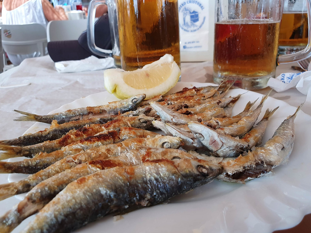 A plate of grilled sardines with a yellow lemon wedge on the side. Behind there are two pints of beer.