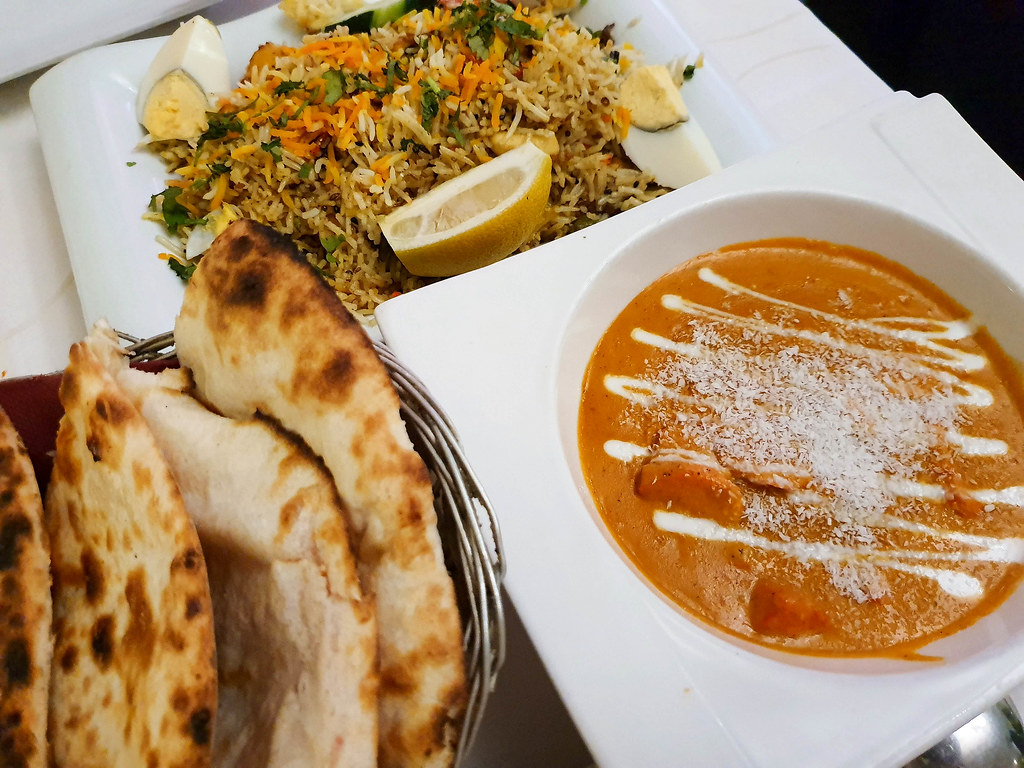 A bowl of orange chicken curry with white cream on top and white coconut flakes decorating it, a basket with four naan breads which have charred marks on them, and a plate with lamb biriany rice with orange shredded carrots on top and green coriander leaves
