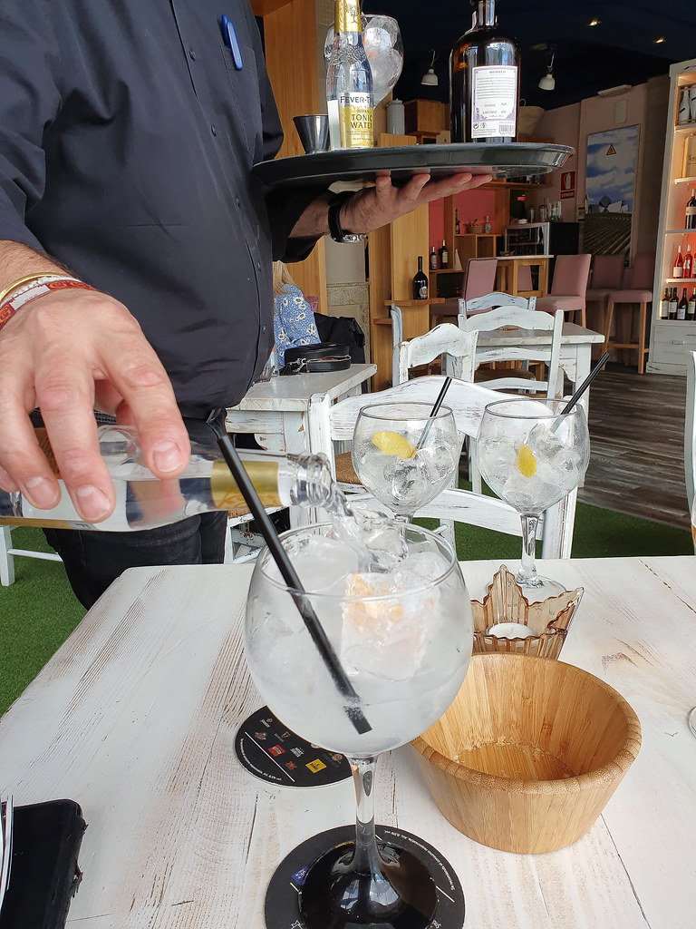 A waiter dressed in black pouring tonic from a bottle to a bowl shaped gin glass
