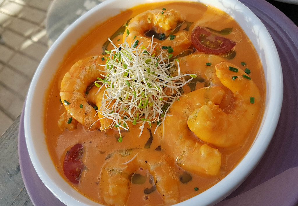 A white bowl filled with prawns in an orange Brazilian sauce, red cherry tomatoes and decorated with a bunch of tiny white beansprouts