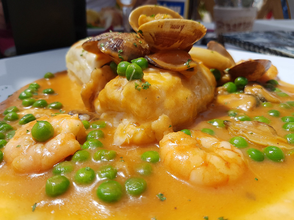 A grilled piece of lubina fish in an orange seafood sauce with green peas in it, with clams and prawns on top