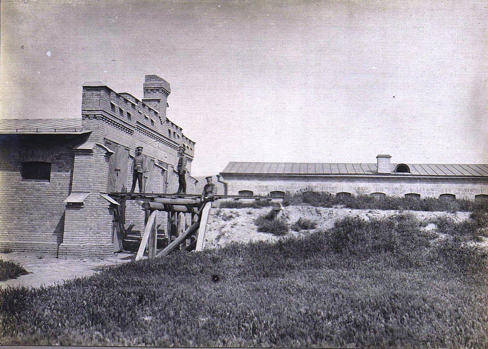 19. Трое военных на брёвнах у здания казармы