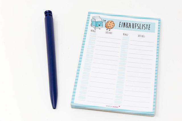 Notizblock für die Einkaufsliste mit Kugelschreiber vor weißem Hintergrund