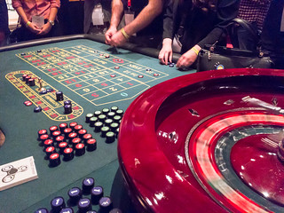 Roulette Table and Roulette Wheel in a Casino with People betting on numbers | by verchmarco