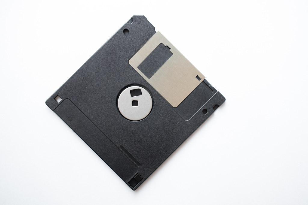 Floppy disk on a white surface. Retro computer tech