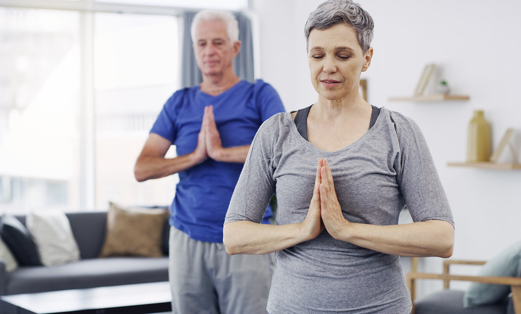 Elderly couple practice yoga at home