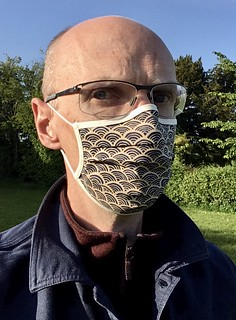Photo of me wearing a cloth face mask with a wave pattern in dark blue on beige