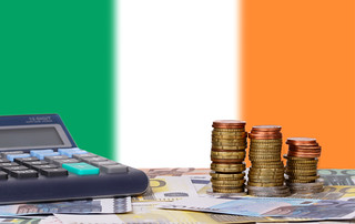 Calculator with money and coins in front of flag of Ireland