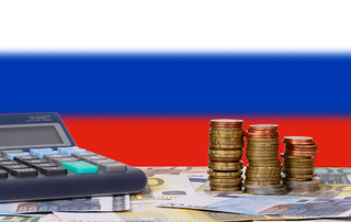 Calculator with money and coins in front of flag of Russia