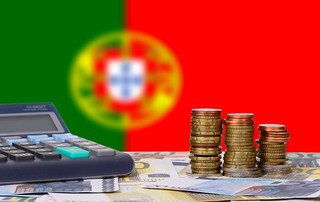 Calculator with money and coins in front of flag of Portugal