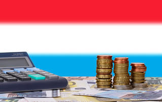 Calculator with money and coins in front of flag of Luxembourg