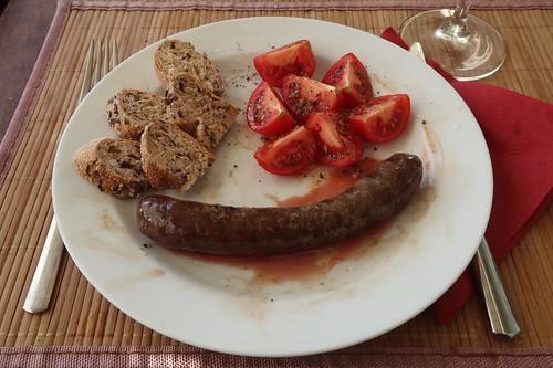 Gegrillte frische Rindsbratwurst mit aufgeschnittenen Tomaten und Urkornweckerl