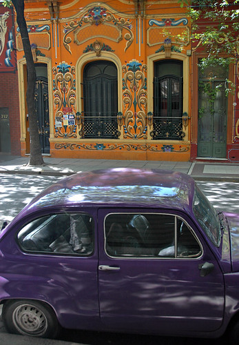 A purple car in front of a brightly painted house done in Fileteado, a style popular in Buenos Aires, Argentina