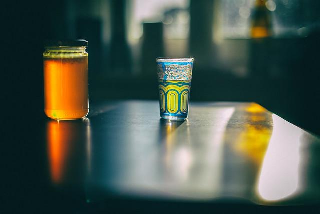 ein Glas Honig, ein Teeglas, eine leere Bierflasche