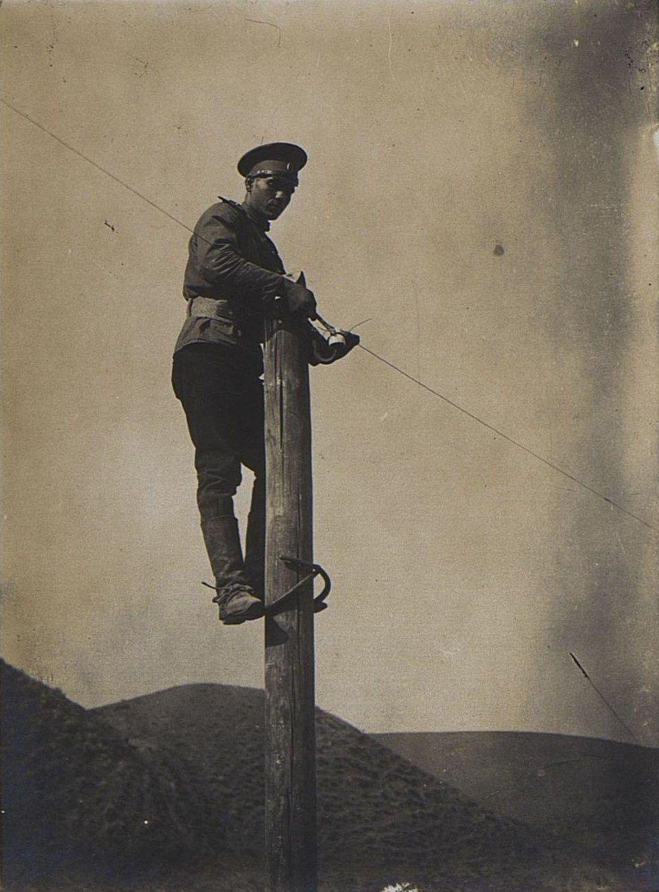 54. Монтировка телеграфной линии. Солдат стоит на столбе, закрепляет проволоку