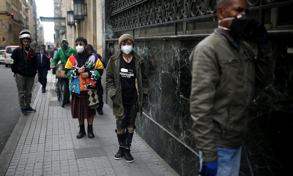 兩名性別認同為非二元性別的跨性別人士於波哥大的銀行外排隊。(圖片來源:Luisa González/Reuters)