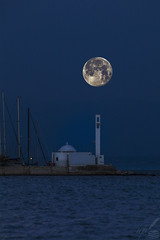 Realistic composite picture of the Flower Moon (lowered to a 3° altitude above horizon) as it sets  over St. Nicholasâs chapel by the Nautical Club in Thessaloniki, Greece. The picture's leading or key element is Moonlight ( « Clair de lune » in French ). Direct moonlight as well as moonlight reflected in the chapel was captured by the camera, for both the moon and the chapel were shot seven minutes before sunrise.   This was the last Super Moon of 2020. The chapel's most prominent architectural feature is the lofty, cross-shaped bell tower. St. Nicholas is the patron saint of members of Hellenic Navy staff and of seafarers in general.  When shot, the Earth's satellite had an 8° 11' altitude above horizon, a 238° azimuth, a -12.49 visual magnitude, 99.3% illumination, 15 days' age and a 362,179 km distance from our planet.  The shutter speed used for the moon was 1/800 sec, whereas for the chapel's exposure it was 1/80 sec. The rest of settings were identical for both shots: f/9 and ISO 320. The 35mm-efl was 480 mm.