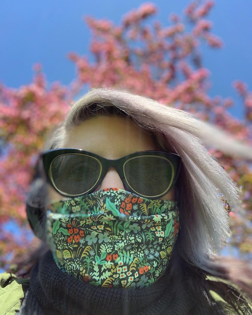 Self with Springy new mask and blossoming trees behind me