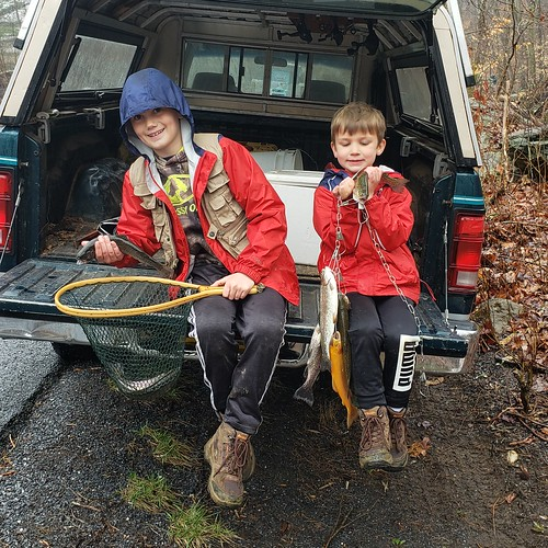 Photo of two boys in a truck holding trout