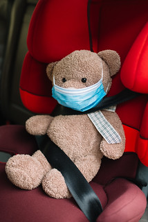 Teddy bear toy in a medical mask is sitting in a child seat in the car. | by shixart1985