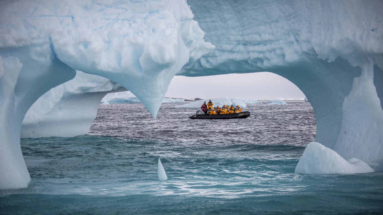 A tour boat behind some glaciers in Antarctica
