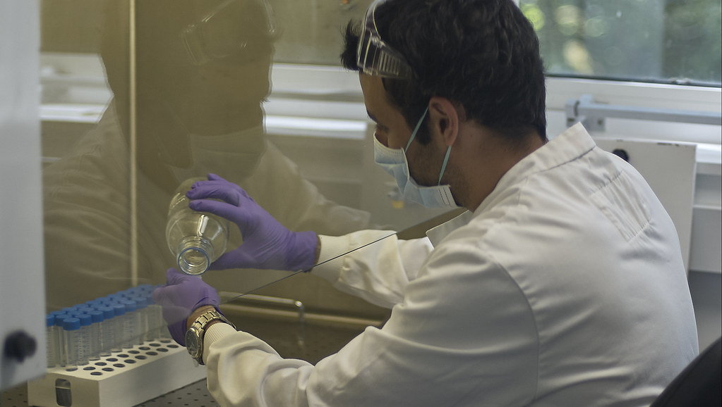 Scientist measuring out chemicals behind a glass screen
