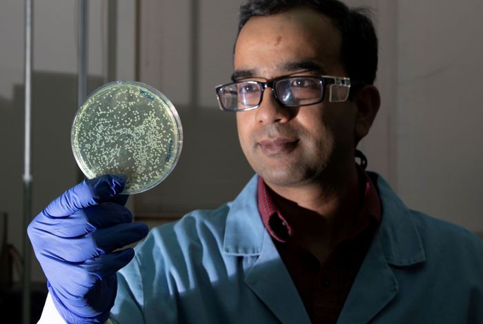 Ramesh Jha demonstrates the Smart Microbial Cell Technology on a petri dish, one of the three possible methods for employing the technology.
