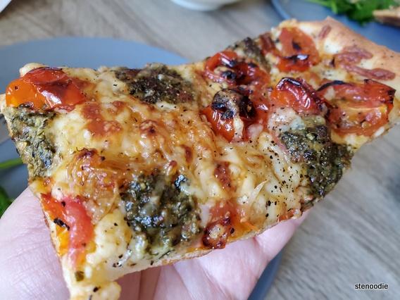 Slice of Pesto Mozzarella Pizza in hand