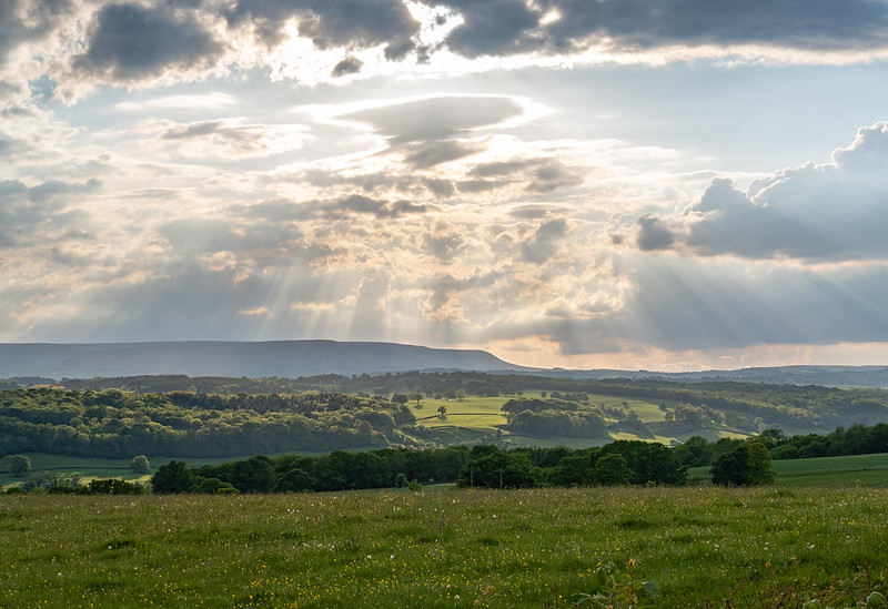 Photo of rays of sunlight fanning down through clouds onto green fields, with a dark ridge on horizon
