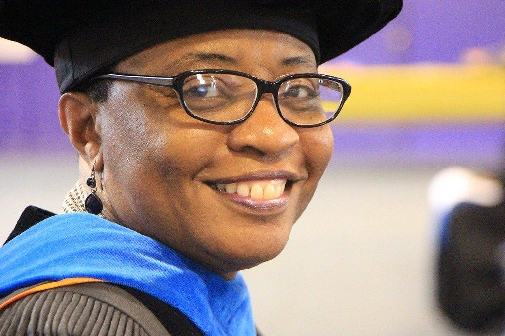 Doctoral graduate and aspiring university professor smiling at graduation ceremony