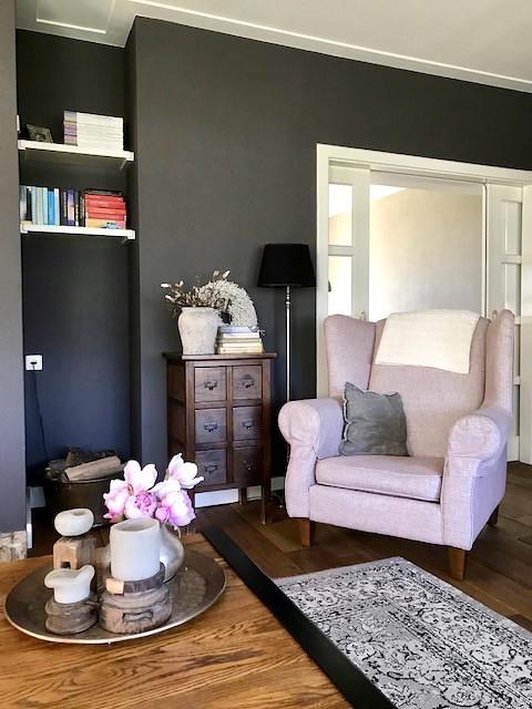 Donkere muur woonkamer roze fauteuil