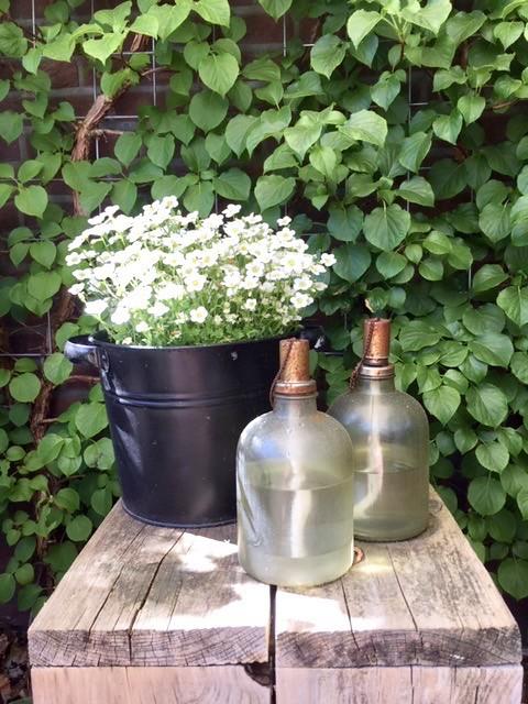 Houten zuil zwart emmertje witte bloemen olieflessen