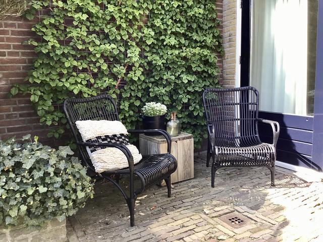 Zwarte rotan stoelen op terras