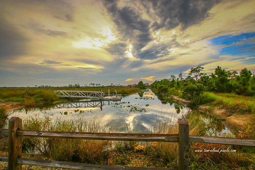 sun sunset clouds cloudy sky bluesky weather landscape water canal reflect reflection kayak launch kayaklaunch nature mothernature outdoors fence rail railfence grass trees bank pineglades naturalarea pinegladesnaturalarea jupiter palmbeachcounty florida usa