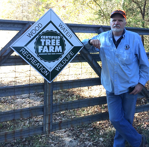 David Helm stands next to a sign that designates his family's property in Chilton County as an Alabama Tree Farm.