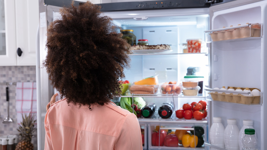 Woman eating from fridge.