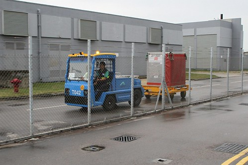 Airport Authority luggage tug transports a Chu Kong Passenger Transport baggage container from SkyPier to the airport
