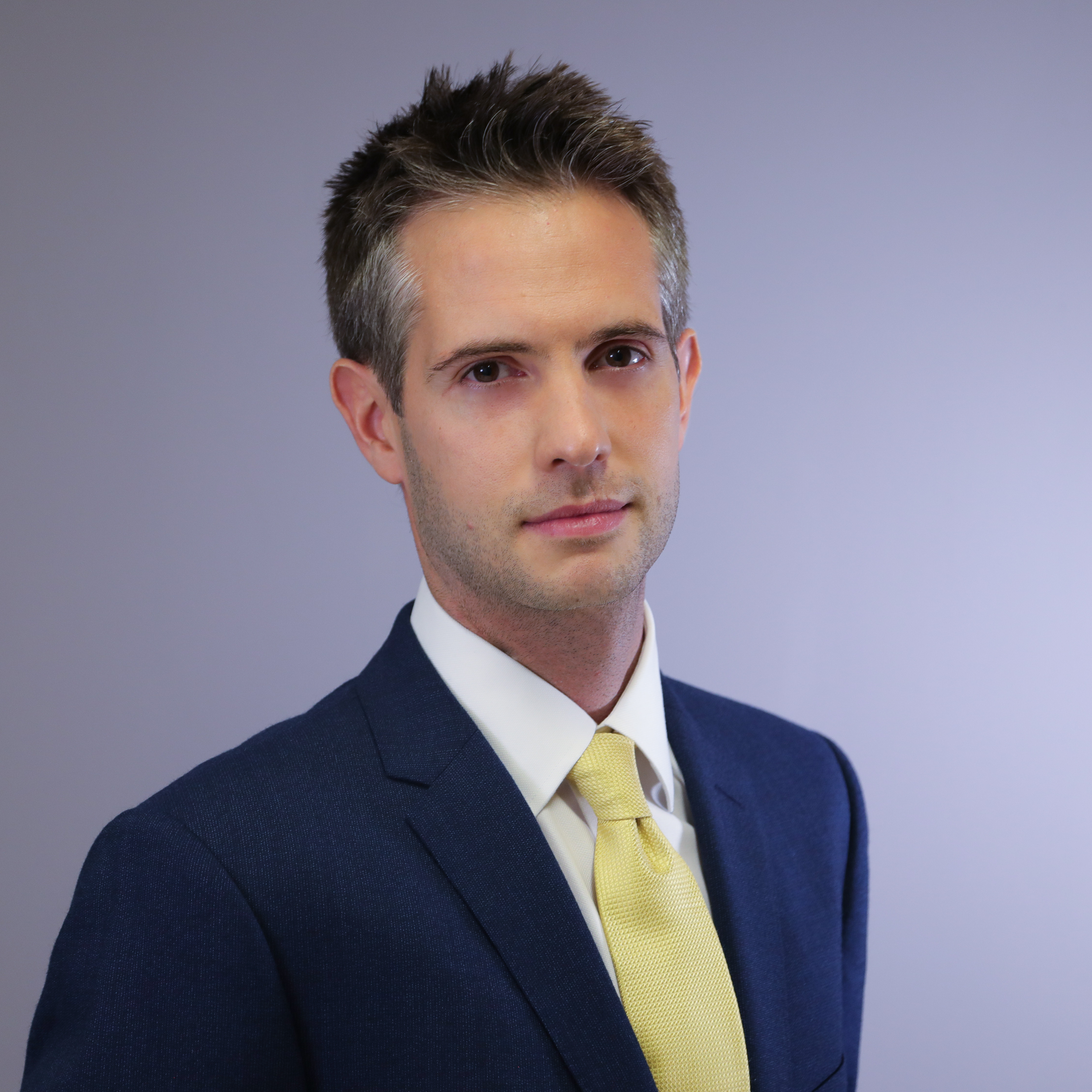 Portrait studio photograph of Dr Ludovic Highman wearing a black suit, white shirt and yellow tie standing in front of a purple background looking towards the camera.