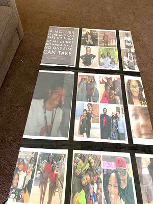 Photo of a black blanket featuring many photos of people, laying on a brown carpet.
