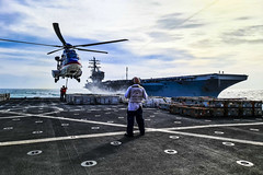 Civilian mariners aboard USNS Carl Brashear (T-AKE 7) attach supplies to Carl Brashear's AS-332 Super Puma helicopter during a replenishment-at-sea with USS Ronald Reagan (CVN 76) in May. (U.S. Navy/DJ Hinahon)
