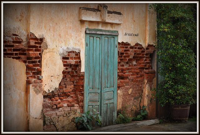 Jirasak's Wall......? avec sa porte prise dans le ciment dans une rue de Savannakhet au Laos Si quelqu'un sait qui est ce Jirasak...Un artiste japonnais? j'arrive rien a trouver .