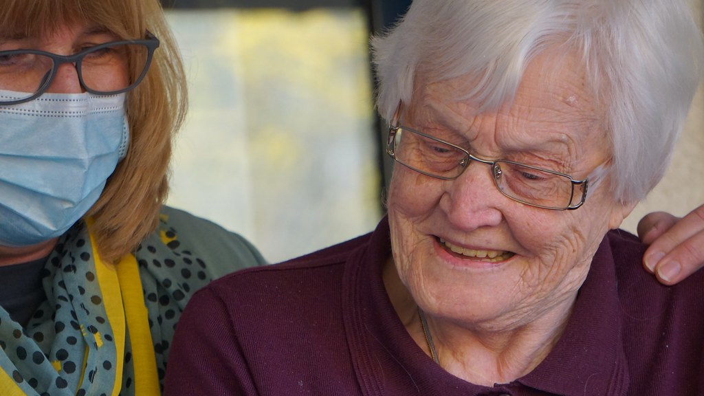 a care worker wearing a mask has her hand on an elderly person's shoulder