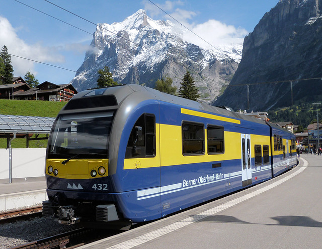 Berner Oberland-Bahn, Switzerland - The 13.49 to Interlaken Ost stands in Grindelwald Station with the Wetterhorn (3,692 m) behind on the 9th September 2019