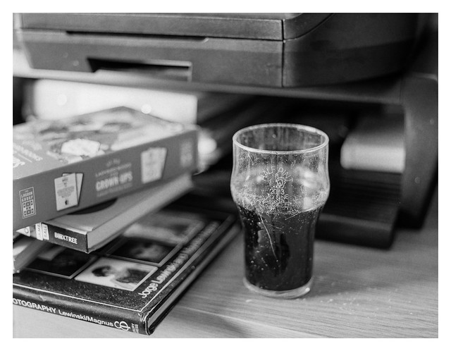 Quarter-pint of flat cola in a scratched glass
