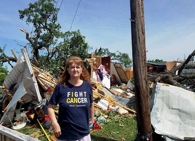 Tornado aftermath: this woman is a tenant and has just lost everything. She stands, in shock, in front of her wrecked rented house