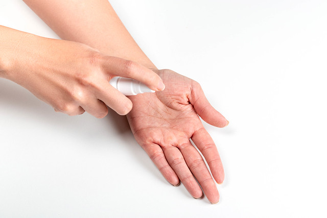 Using an antiseptic spray to disinfect hands on a white background