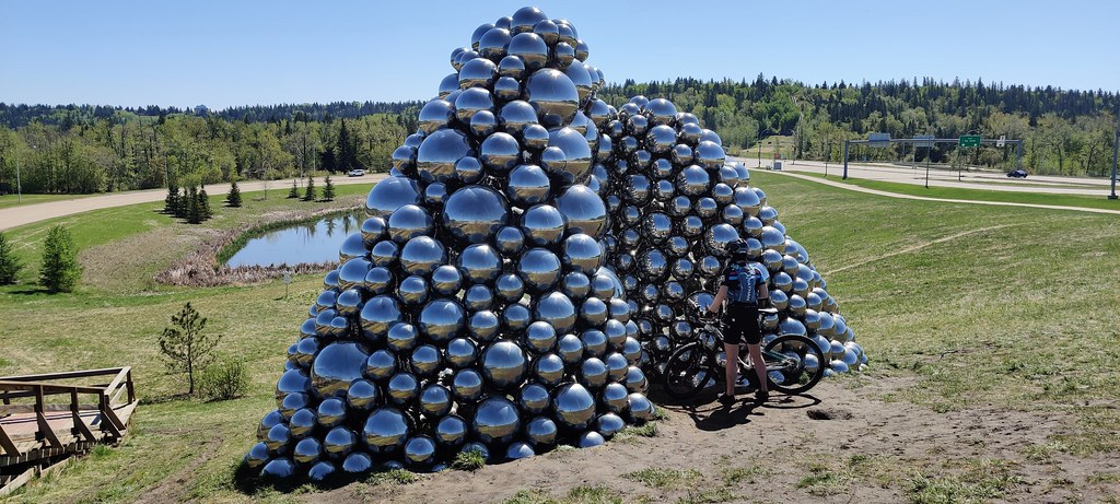 A cyclist examines the shiny balls that make up the Talus Dome, a piece of public art near the Quesnell Bridge